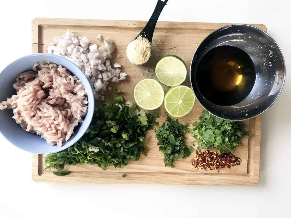 Ingredients for larb gai thai chicken salad on a wooden cutting board, ingredients shown are minced chicken, chopped shallots, chopped green onion or spring onion, halved limes, khao kua which is toasted rice, chopped cilantro or coriander, chopped mint, chili flakes and a mix of fish sauce, sugar and water
