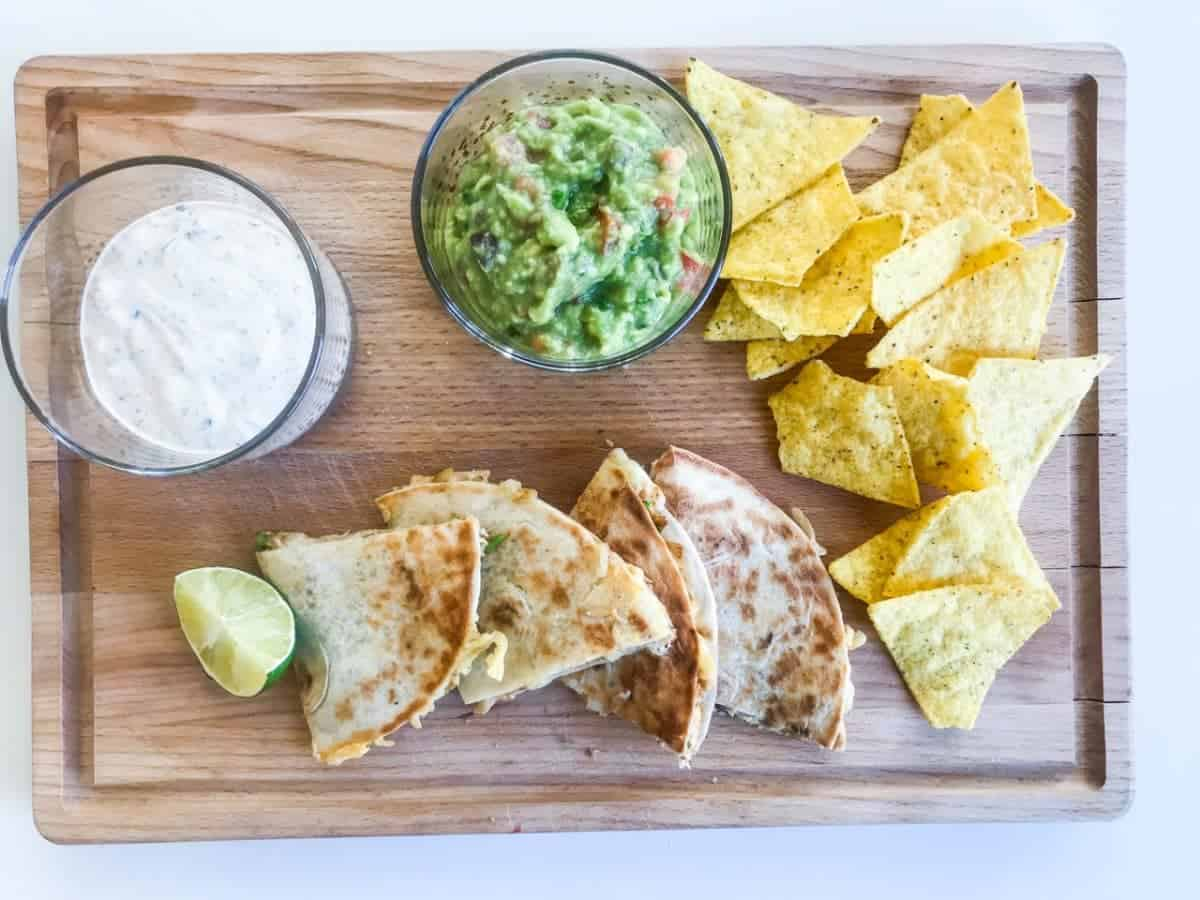 Quesadilla cut in pieces on a wooden choppingboard with a lime slice, guacamole, ranch dip and tortilla chips