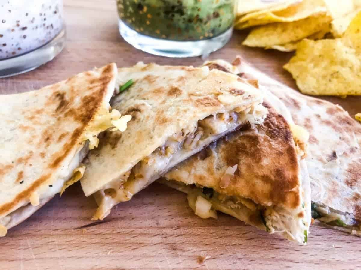 Close up of chicken quesadillas cut in pieces on a wooden choppingboard with guacamole, ranch dip and tortilla chips