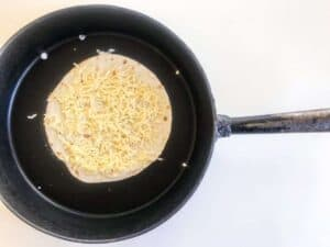 Step two of cooking Chicken Quesadillas - Tortilla topped with cheese in a black pan on a white surface