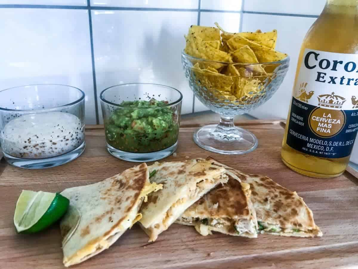 Chicken quesadillas cut in pieces on a wooden chopping board with lime slices, guacamole, ranch dip, tortilla chips and a Corona beer
