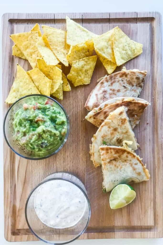 chicken quesadillas on a wooden chopping board