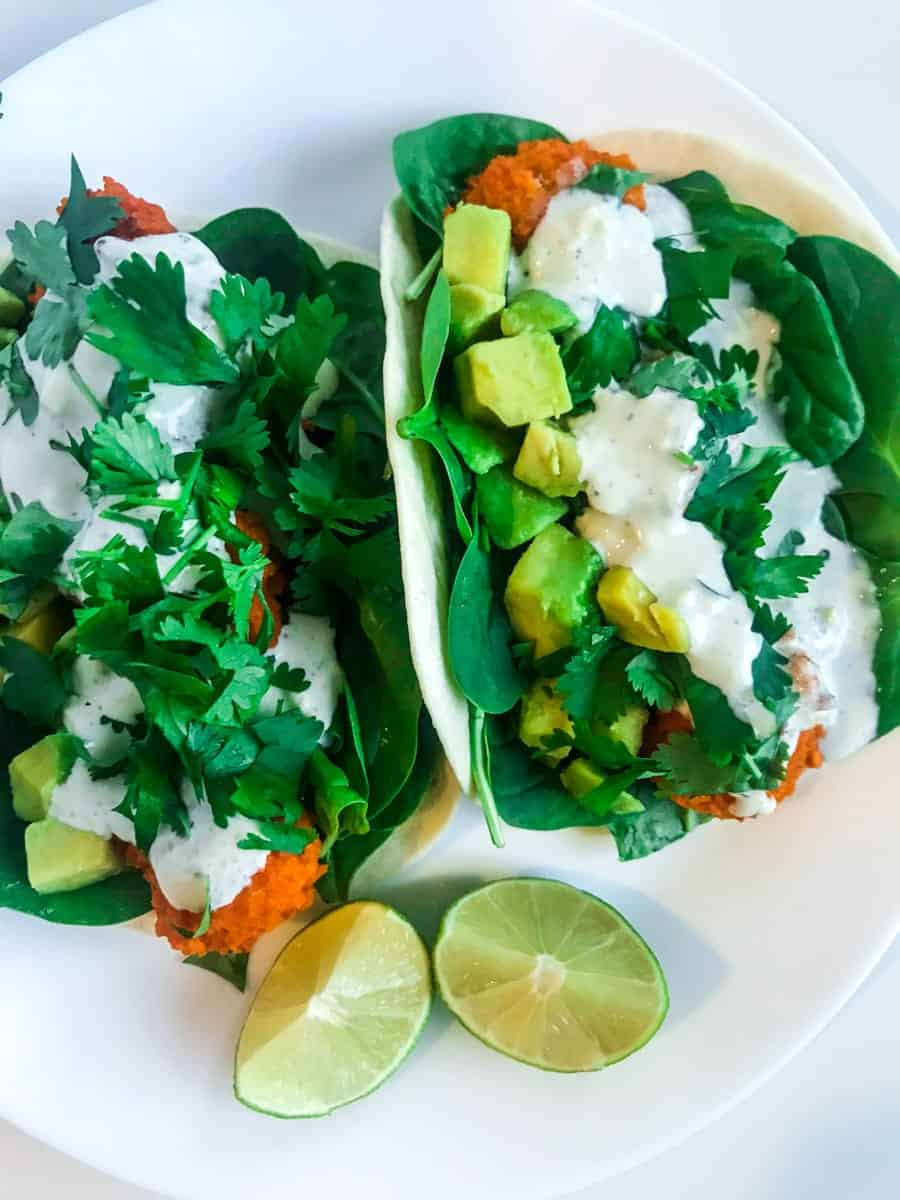 Buffalo cauliflower tacos with lime on a white plate