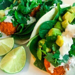 Buffalo cauliflower tacos with lime on a white plate
