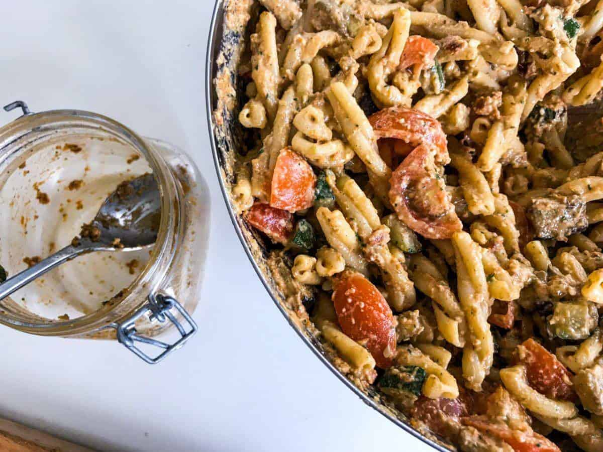 Red pesto pasta with roasted veggies in a bowl on white surface