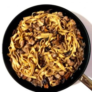 Creamy red wine chicken pasta with chanterelles and white button mushrooms in black pan on white surface