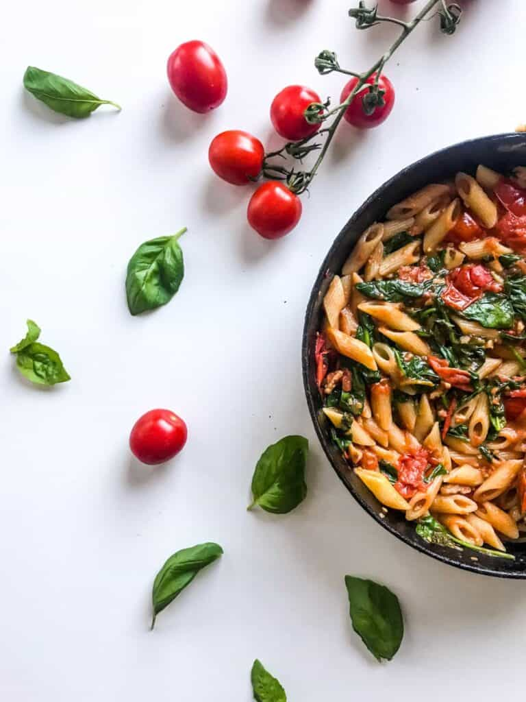 15-minute cherry tomato pasta with spinach and walnuts in a black skillet on a white table decorated with cherry tomatoes on a branch and basil leaves