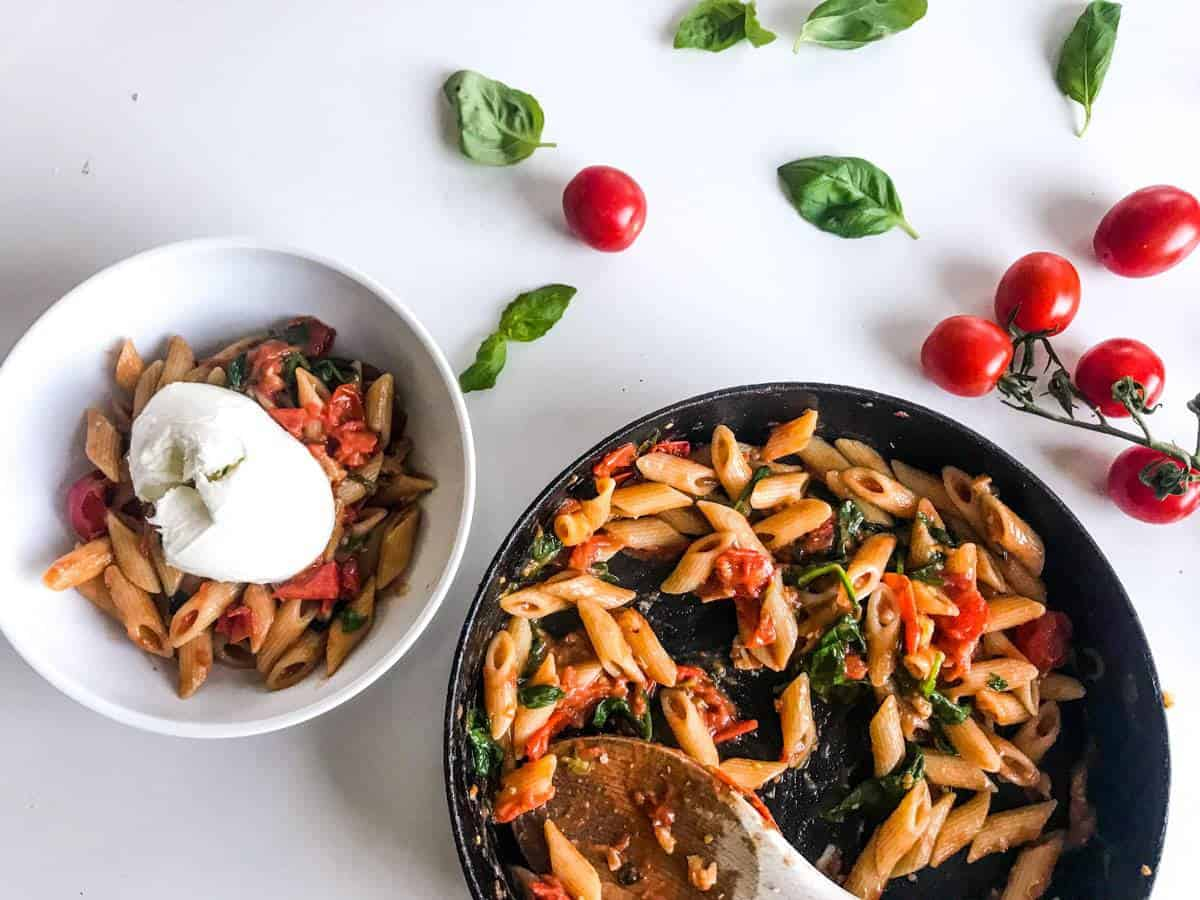 15-minute cherry tomato pasta with spinach and walnuts in a black skillet and in a white bowl topped with burrata, all on a white table decorated with cherry tomatoes on a branch and basil leaves
