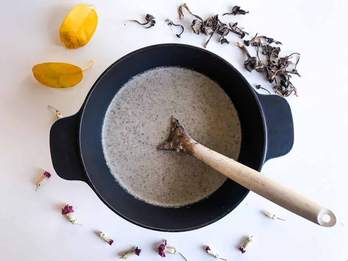 Cream of Mushroom Soup in a pan with a wooden spoon, on a white table decorated with yellow leaves, dried flowers and dried mushrooms