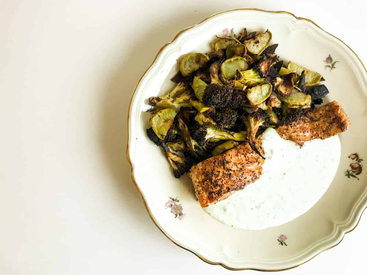 Lemon Pepper Salmon with Garlic Roasted Broccoli and Feta Yoghurt Sauce on a plate