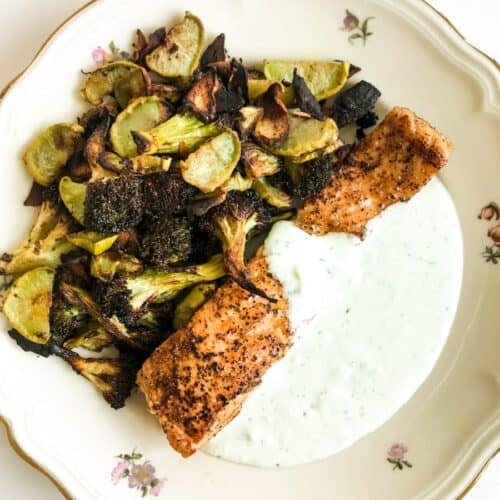 Lemon Pepper Salmon with Garlic Roasted Broccoli and Feta Yoghurt Sauce on a plate