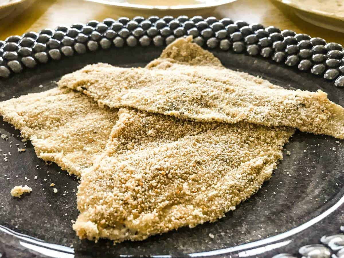 Three breaded plaice filets on a black plate for pan-seared breaded plaice with whipped lemon butter