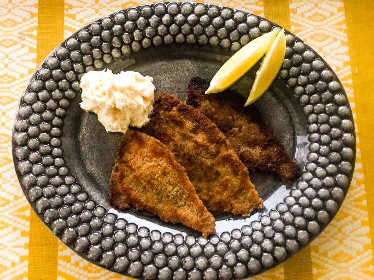 Pan-seared breaded plaice with whipped lemon butter and lemon wedges on a black plate on a yellow table