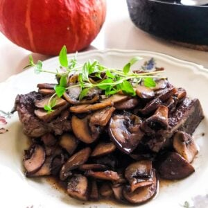 Quick one-pan pork chops and mushrooms with red wine and thyme in a black cast iron skillet