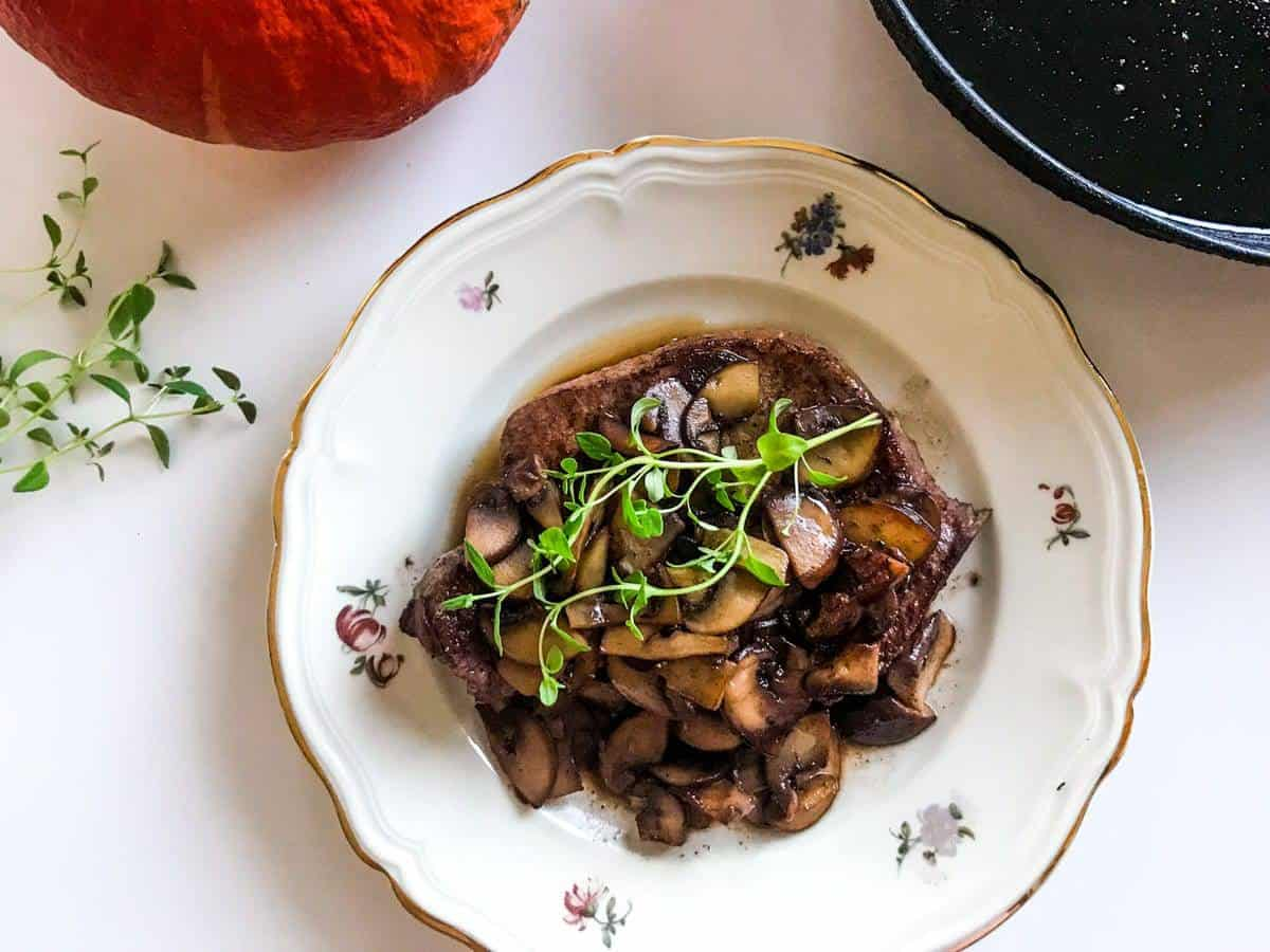 Quick one-pan pork chops and mushrooms with red wine and thyme on a plate on a white surface with a pumpkin and a black cast iron skillet and some thyme
