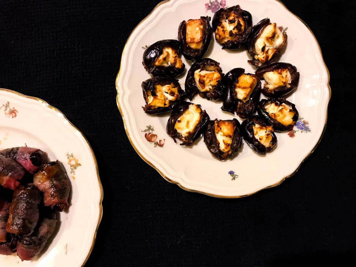 Savory dates two ways - bacon wrapped and feta stuffed, here cooked and plated on a black surface