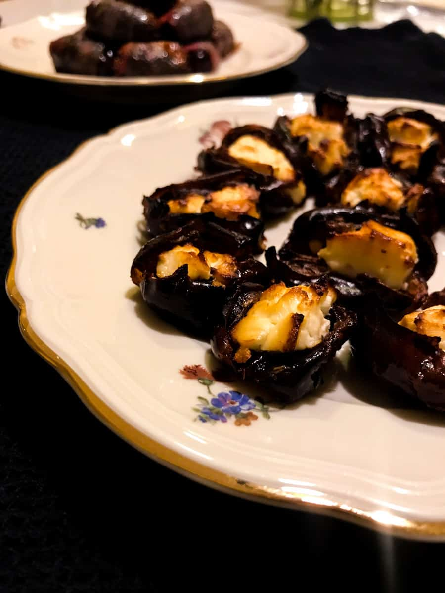 Savory Bacon Wrapped Dates and Feta Stuffed Dates, here cooked and plated on a black surface