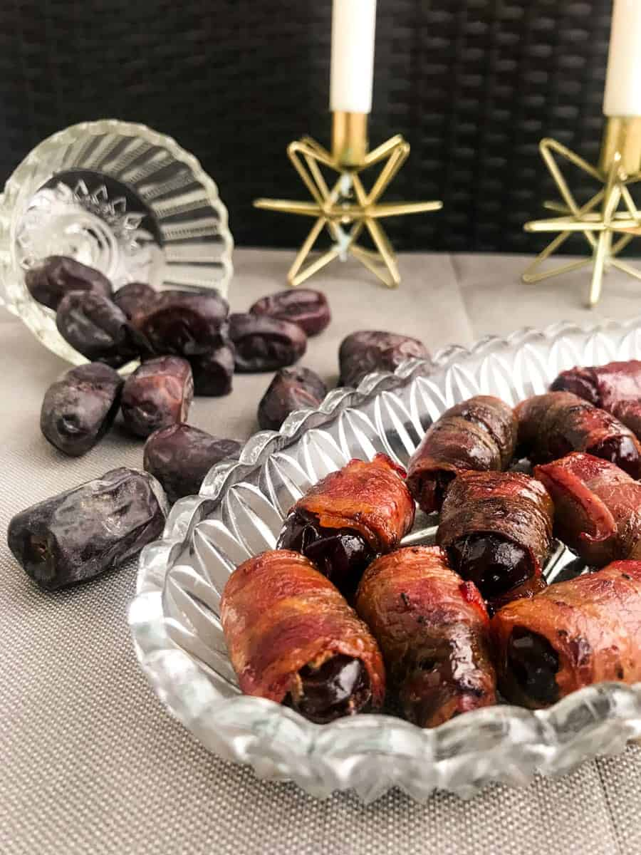 bacon wrapped dates on a glass plate with dates in the background
