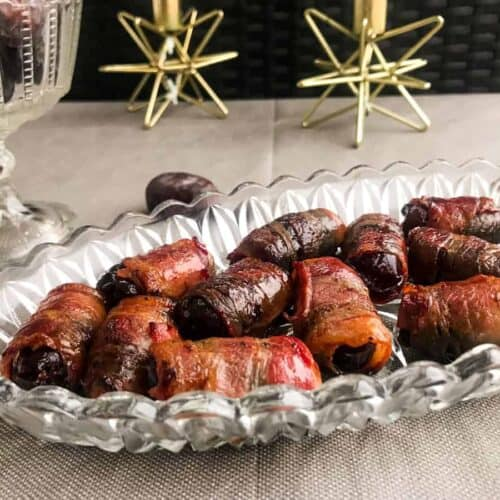bacon wrapped dates on a glass plate