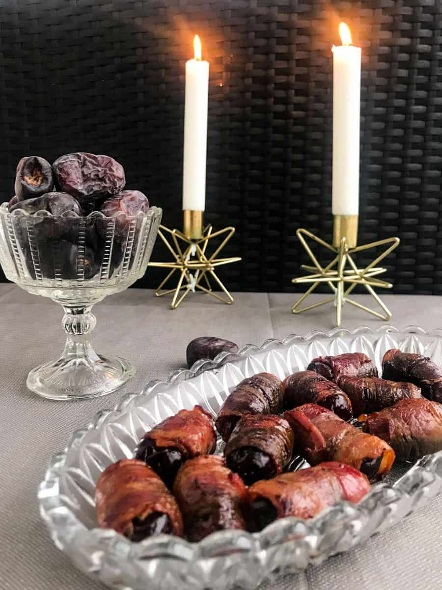 bacon wrapped dates on a glass plate with dates and candles in the background