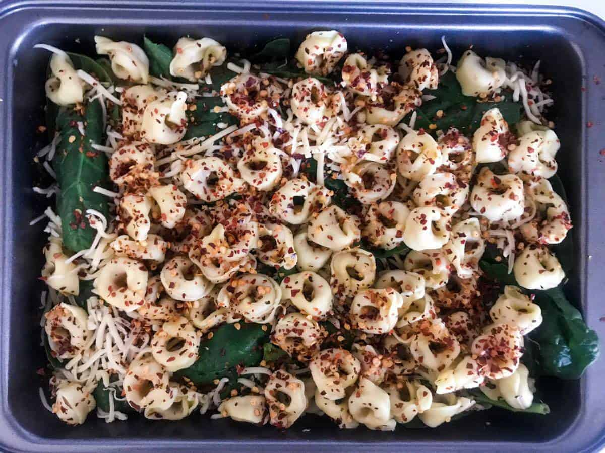 Half-cooked tortellini, spinach, cheese and chili flakes in a pan