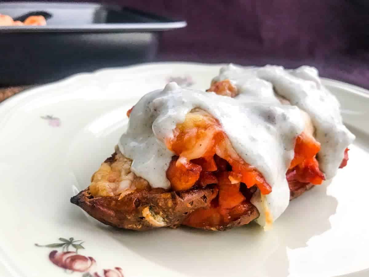 Buffalo bacon loaded sweet potato skins with blue cheese dressing on a purple surface