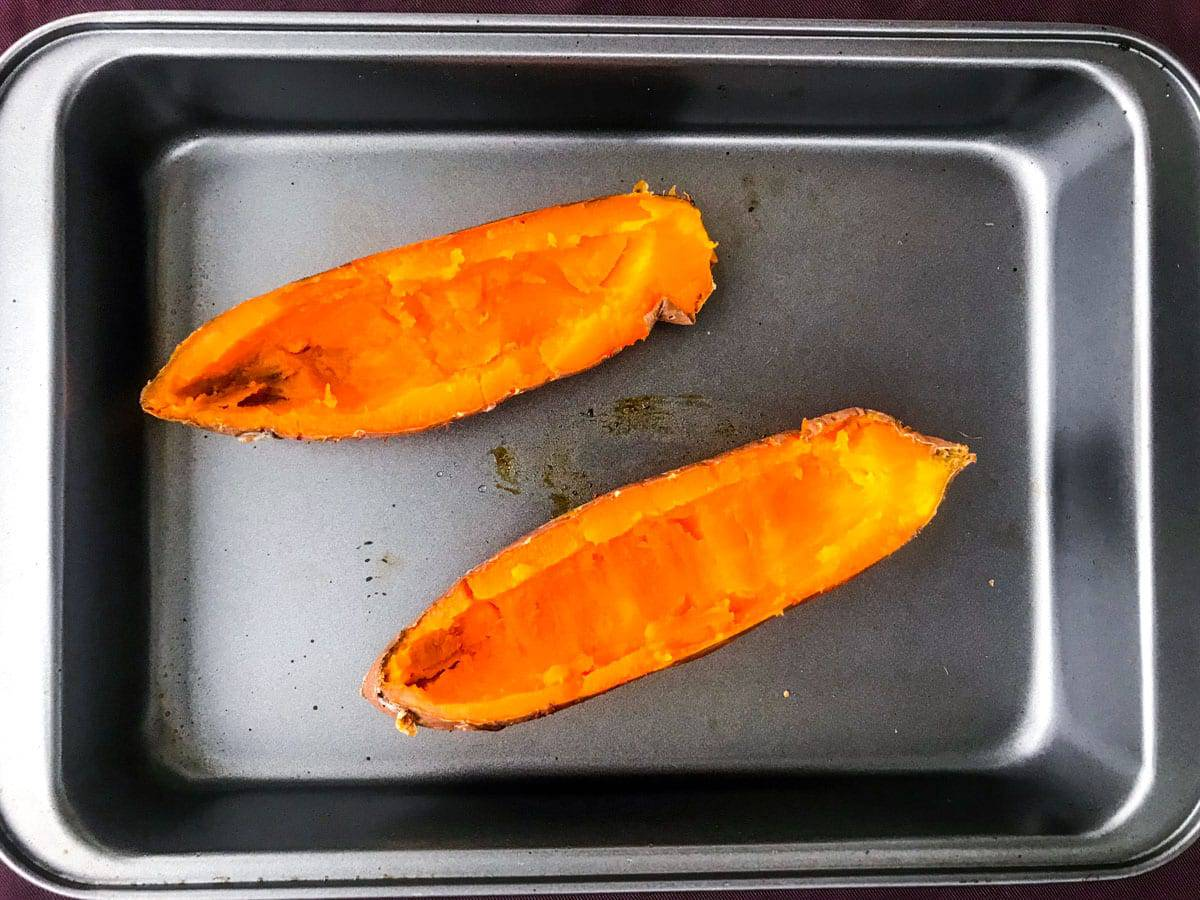 top down view of two sweet potato halves in a deep oven dish