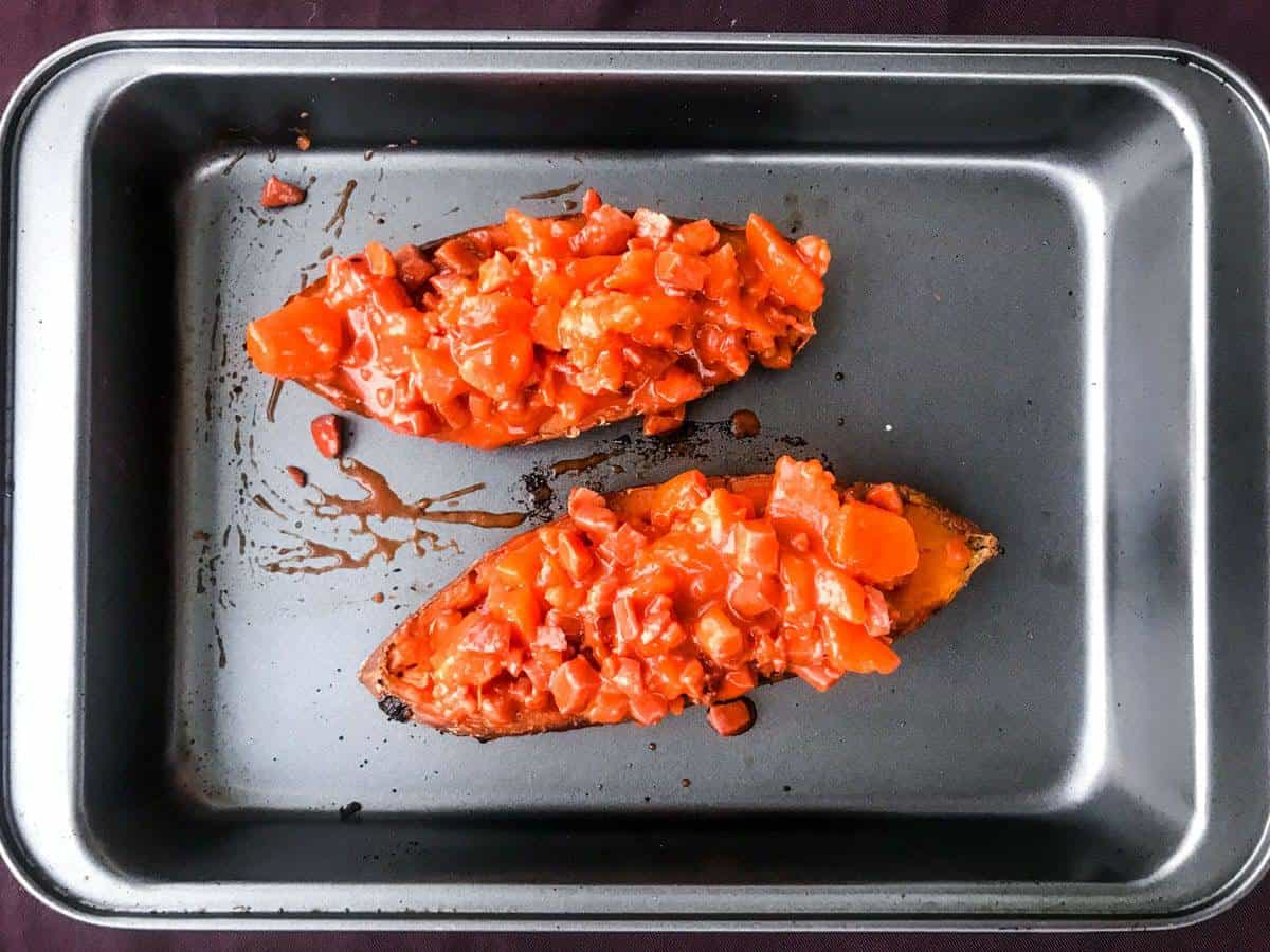 top down view of two sweet potato halves in a deep oven dish loaded with buffalo bacon