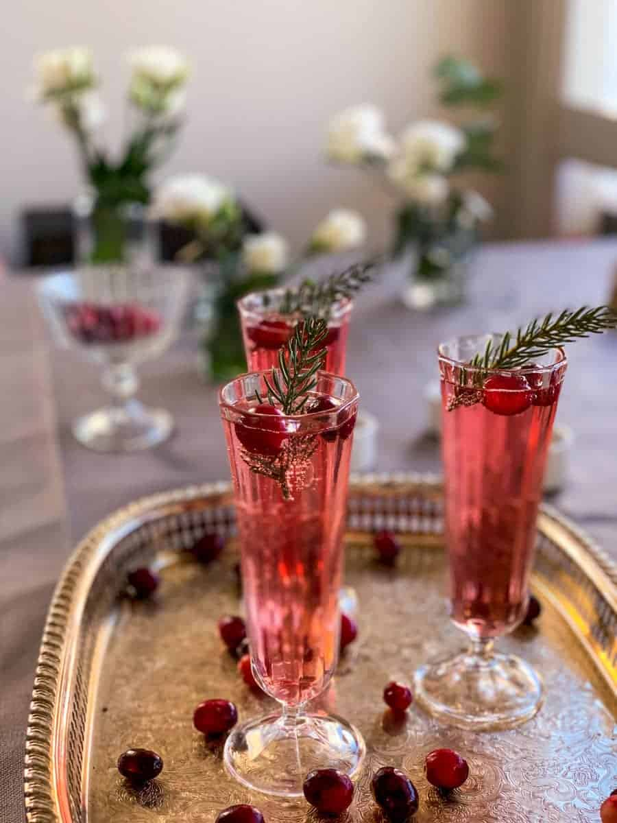 3 cranberry champagne cocktails on a silver platter