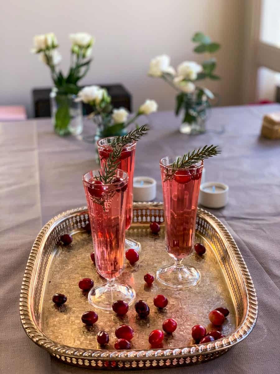 3 glasses of cranberry champagne cocktail and fresh cranberries