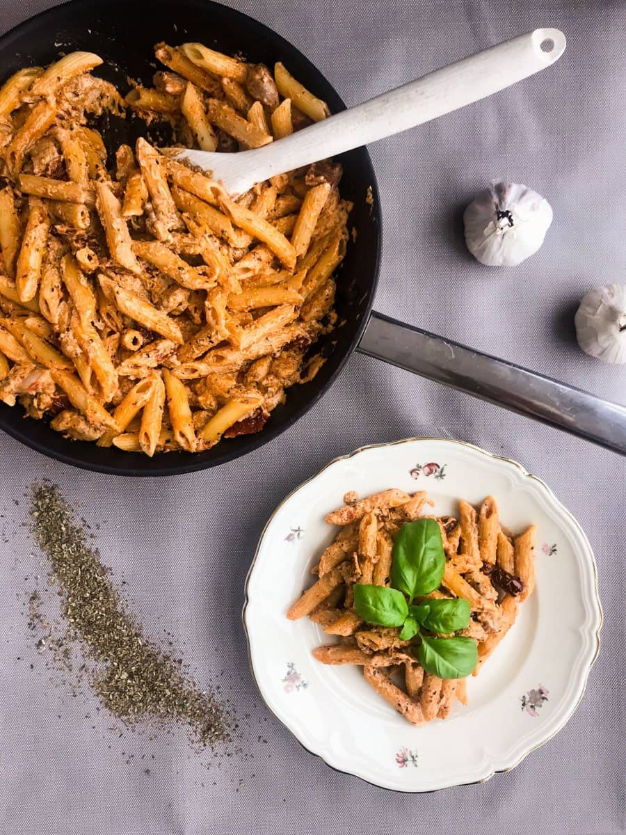 Creamy Sun-Dried Tomato Chicken Pasta with Crème Fraiche in a black pan and in a plate on a grey surface with garlic and basil