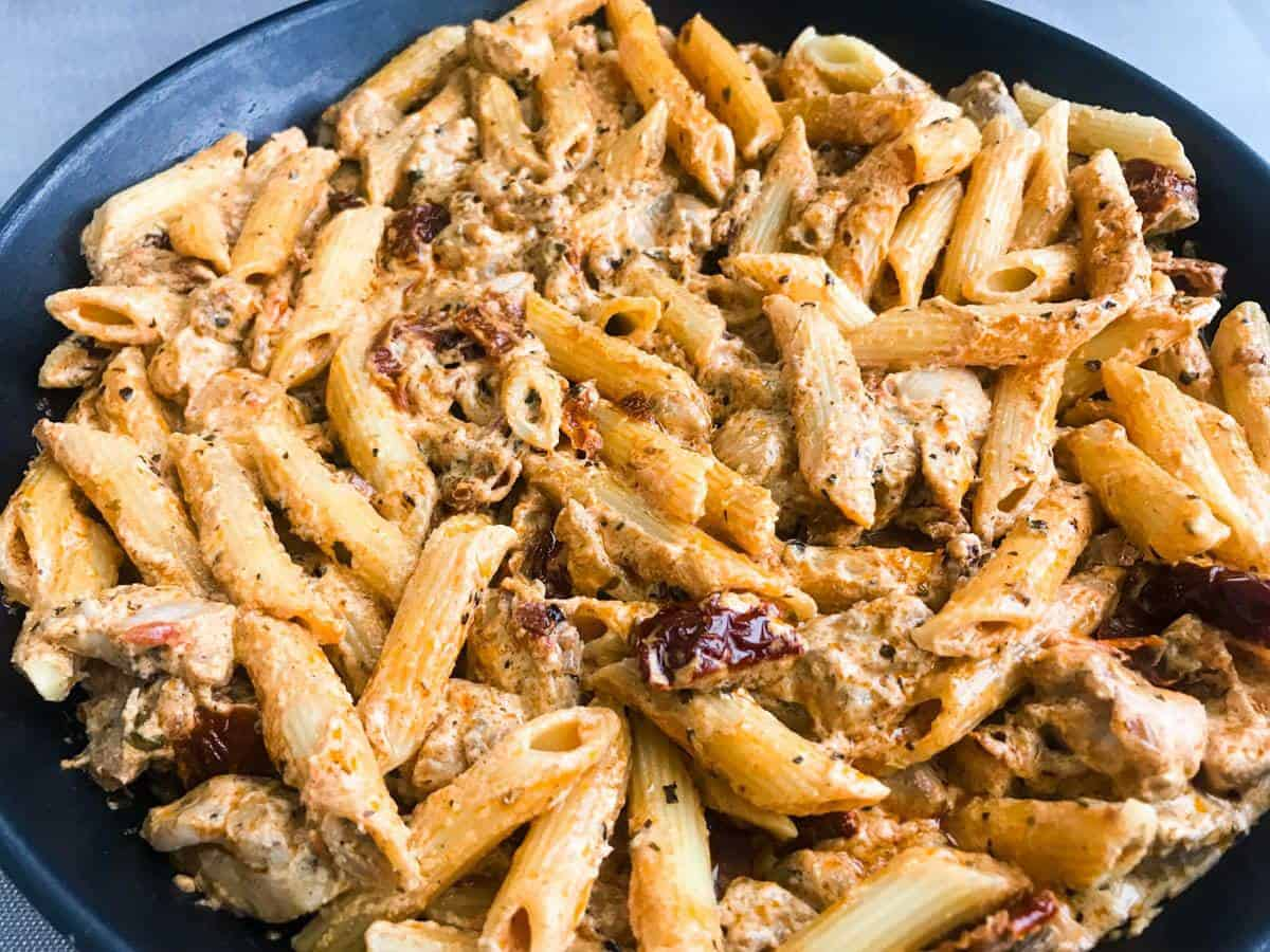 Close-up of Creamy Sun-Dried Tomato Chicken Pasta with Crème Fraiche in a black pan