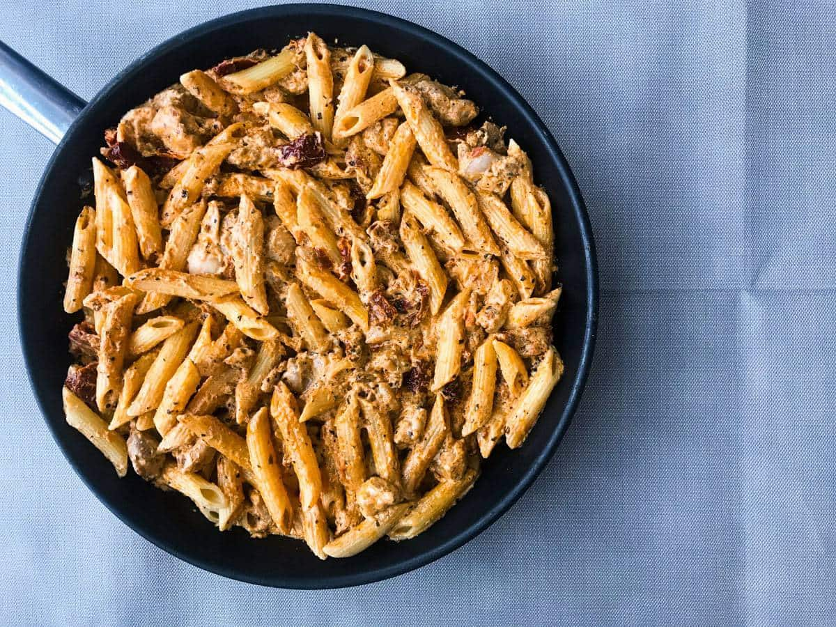 top down view of sundried tomato pasta with chicken in a skillet
