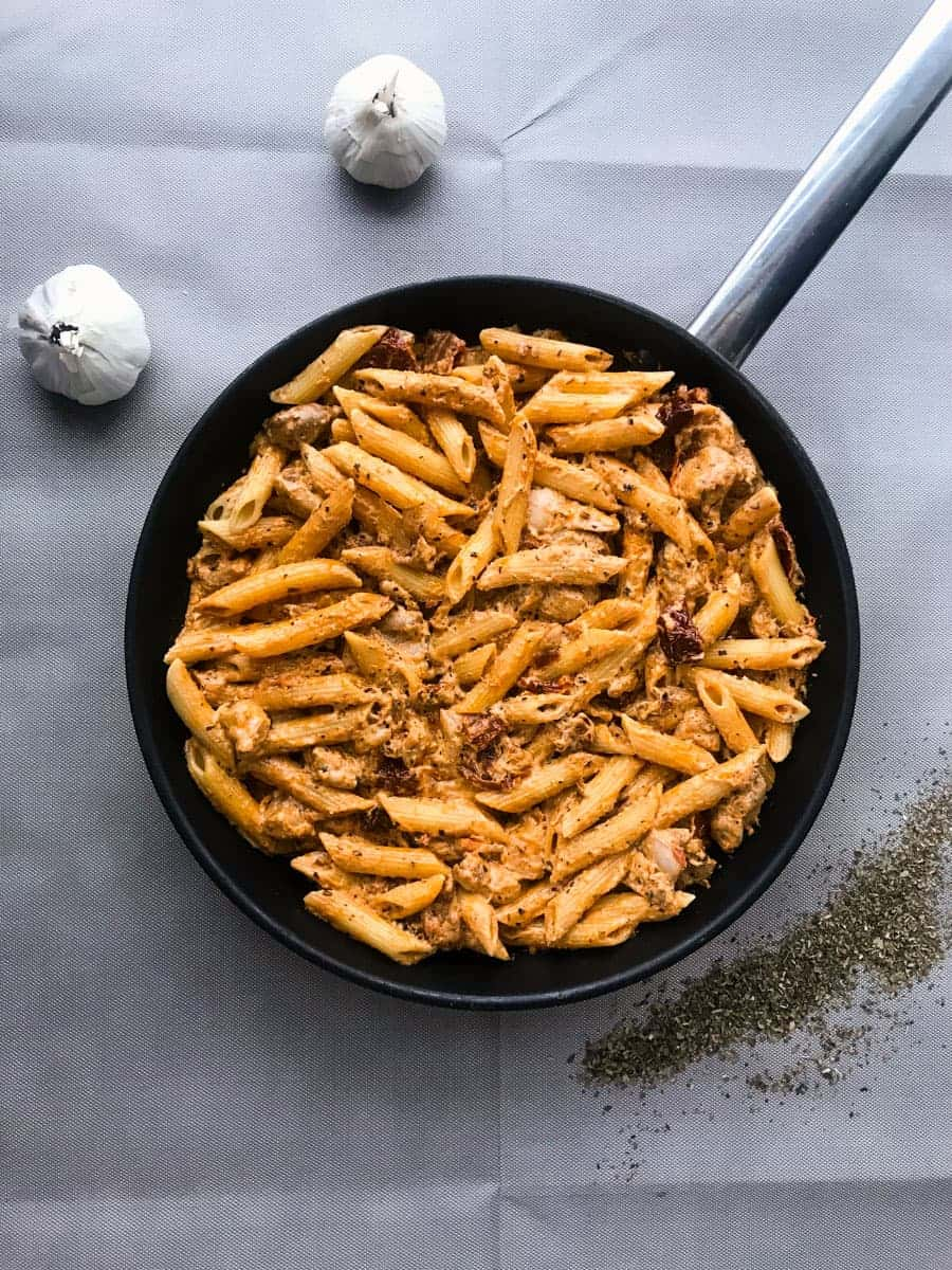 Creamy Sun-Dried Tomato Chicken Pasta with Crème Fraiche in a black pan on a grey surface with garlic and basil