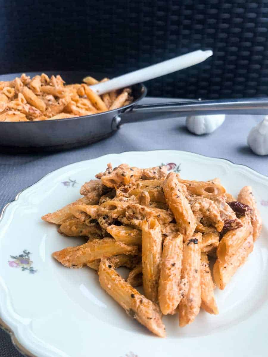 Creamy Sun-Dried Tomato Chicken Pasta with Crème Fraiche in a black pan and in a plate on a grey surface with garlic