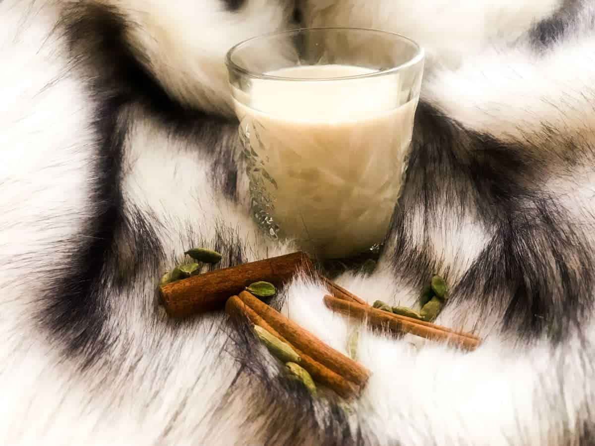 homemade chai latte with cinnamon rods and green cardamom pods