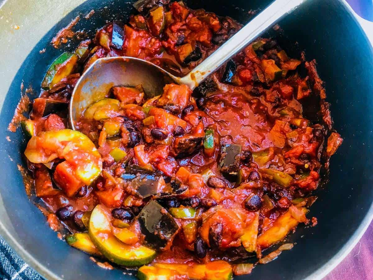 Vegan black chili in a crockpot with a ladle