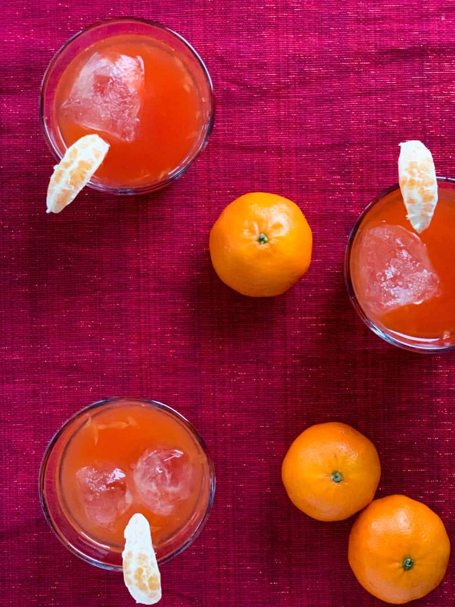 three glasses of clementine campari cocktail with three clementines