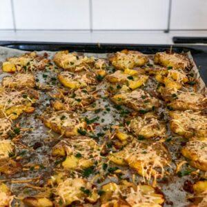 crispy garlic parmesan smashed potatoes on an oven tray