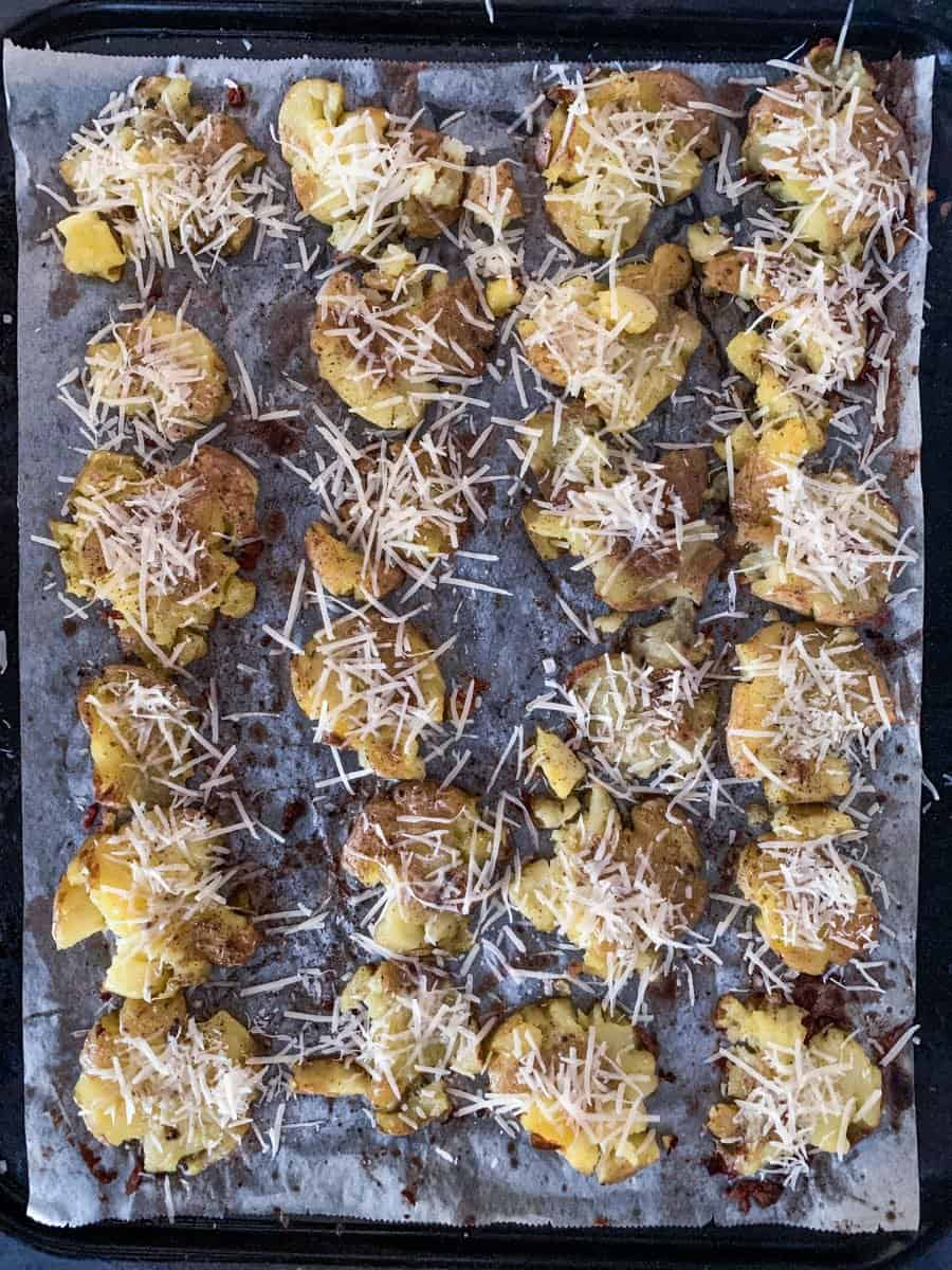 crispy garlic parmesan smashed potatoes on an oven tray