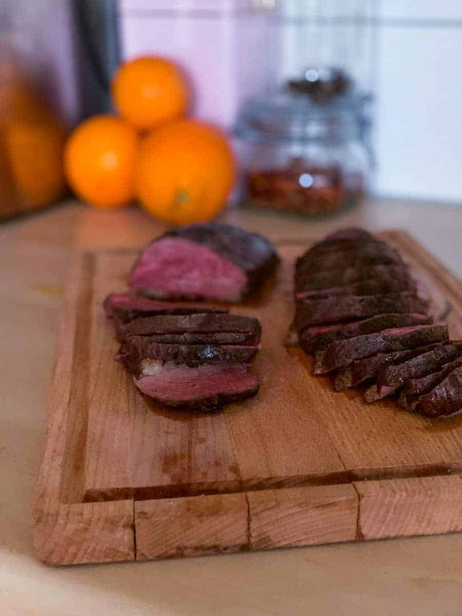 sliced duck breast on a wooden chopping board
