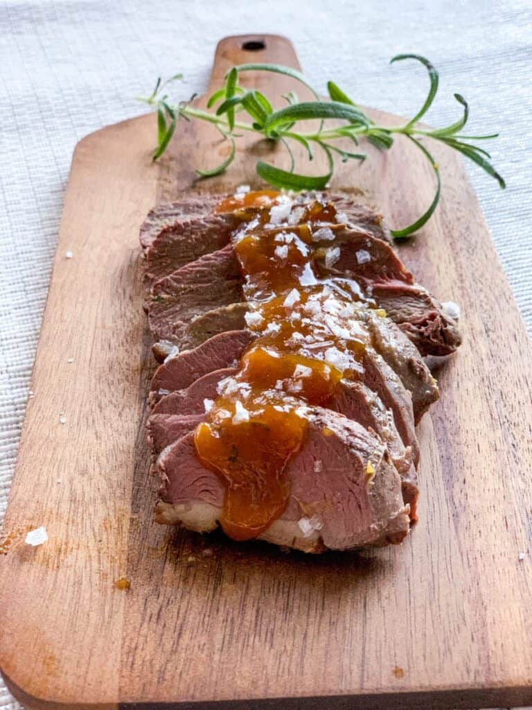 duck a lorange duck in orange sauce cut up on a wooden chopping board