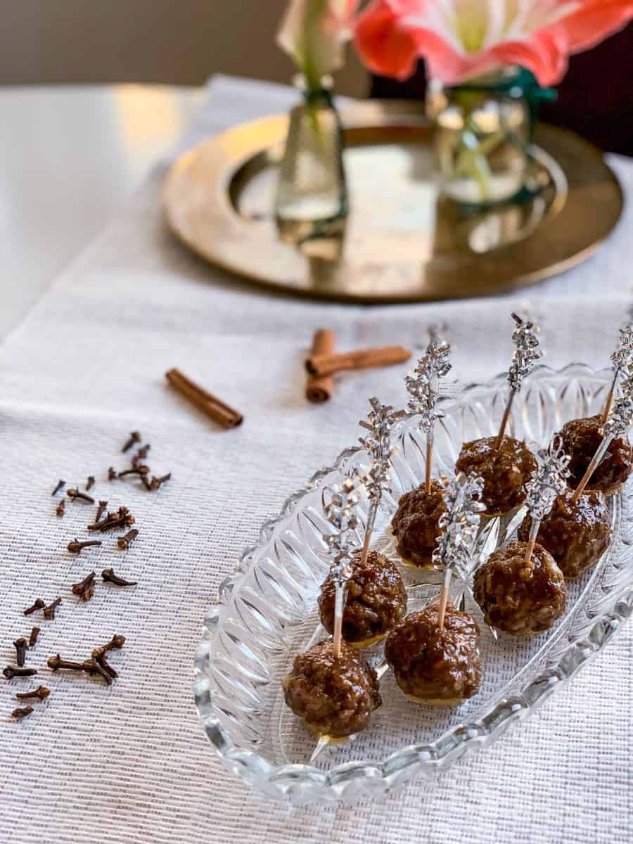 honey balsamic glazed gingerbread spice meatballs with tooth picks on a glass platter