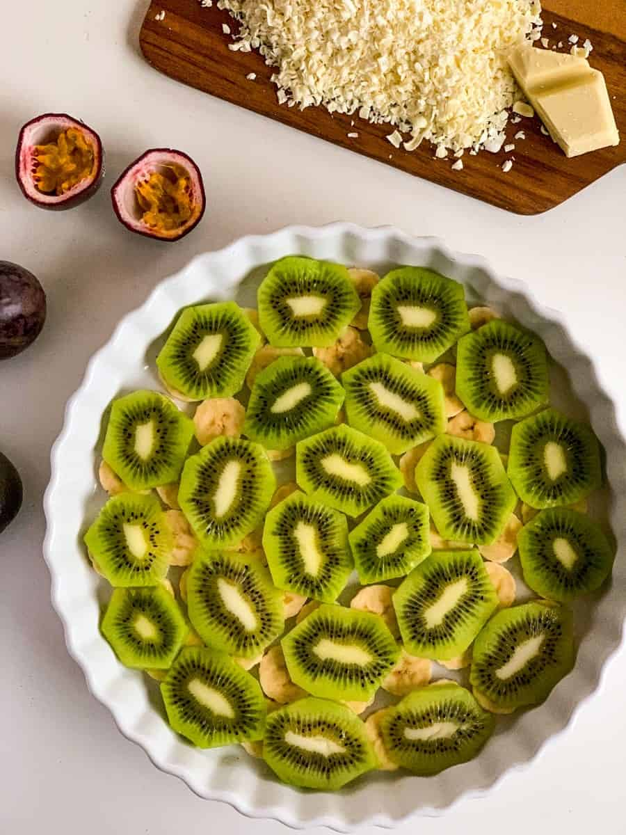 bananas and kiwis in a pie dish for passion fruit gino fruit bake with passion fruit and white chocolate