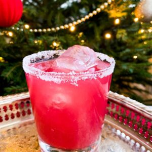 sober santa christmas punch in a glass on a silver platter in front of a decorated christmas tree
