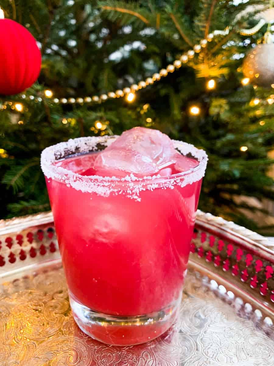 sober santa non-alcoholic christmas punch in a glass on a silver platter in front of a decorated christmas tree