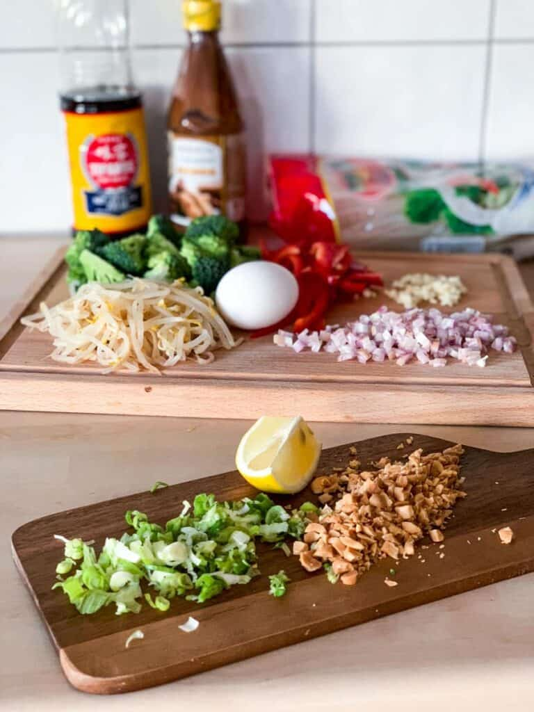ingredients for veggie pad thai on two wodden choppign boards