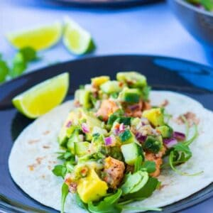 side view of a healthy salmon fish taco with ginger avocado salsa, and a lime wedge