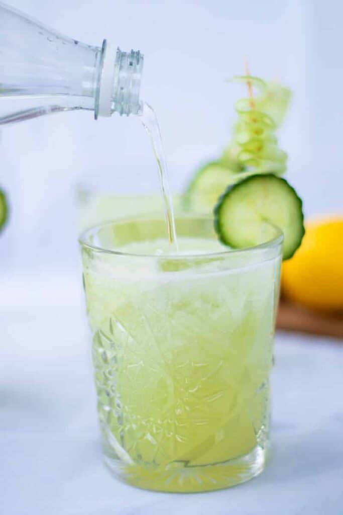 side view of a clean cucumber collins with soda water being poured into the glass