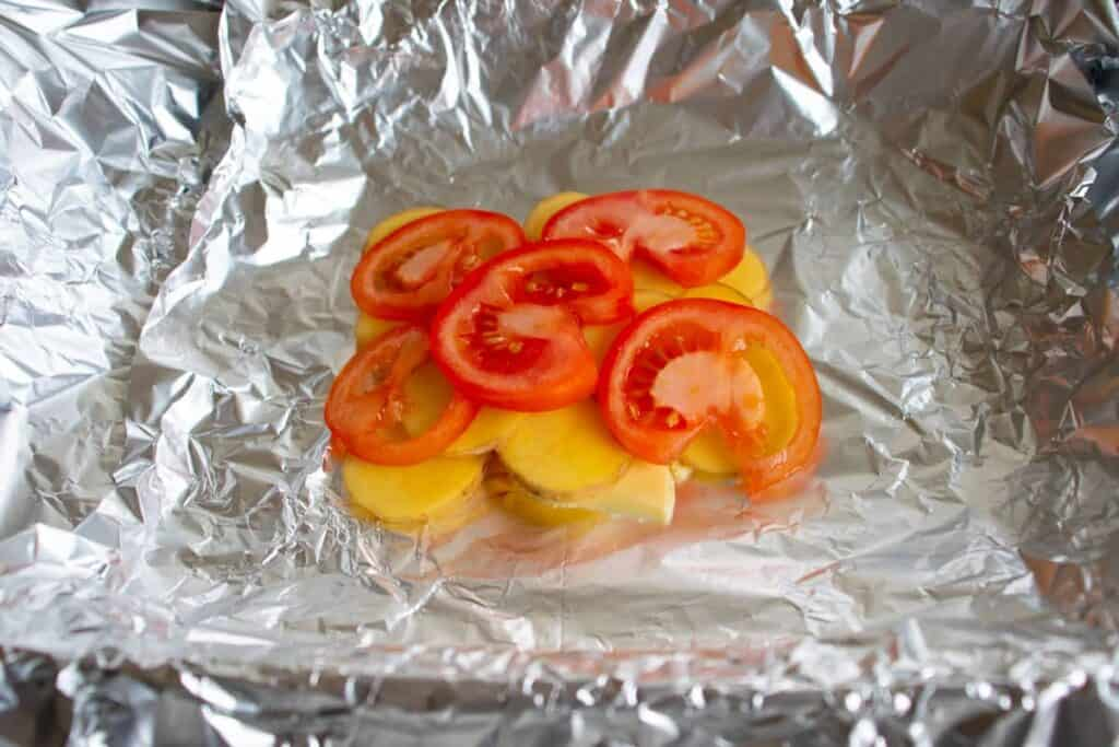 butter, potatoes and tomatoes on aluminium foil